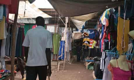 A man walks in a market stalls selling secondhand clothes in Juba