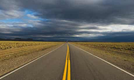 Storm clouds gather over an empty road