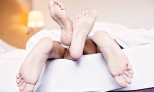 Feet of a couple in the bed