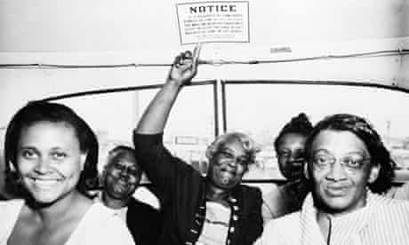 Black women celebrate the outlawing of segregation signs on an American bus