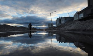 Man walks by standing water and piles of sand swept onto a road from superstorm Sandy
