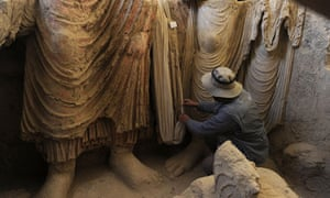 An Afghan archaeologist examines the remains of statues of Buddha at Mes Aynak.