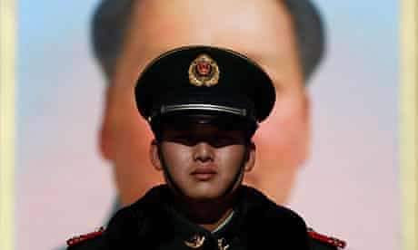 A policeman guards a giant portrait Mao in Beijing
