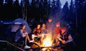 Group of people sitting by campfire