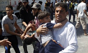 Palestinians carry injured people following shelling of UN school in Rafah
