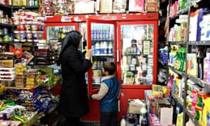 An Iranian woman and a boy shop at a gro