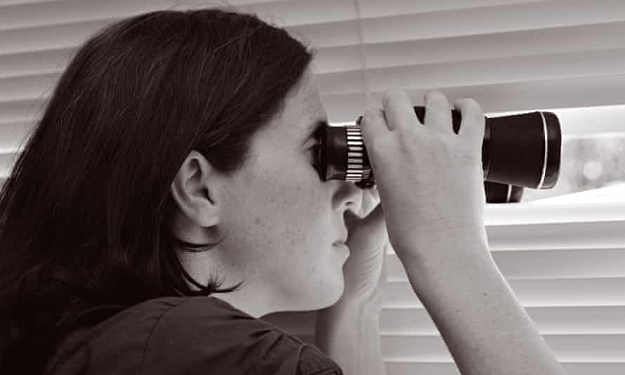 A woman spies through a window with binoculars