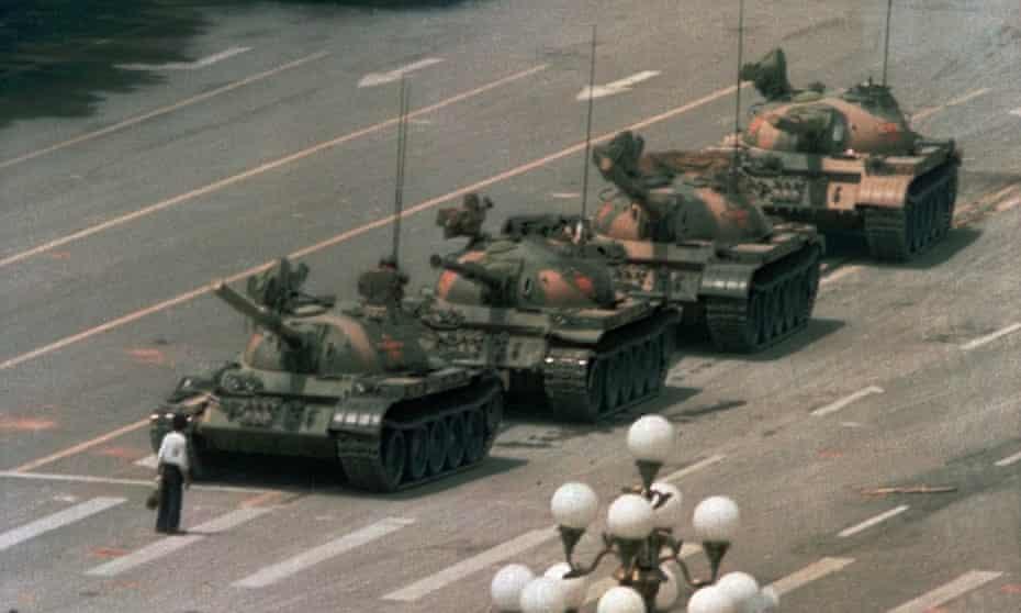 A pro-democracy protester blocks a line of tanks in Tiananmen Square on 4 June 1989.