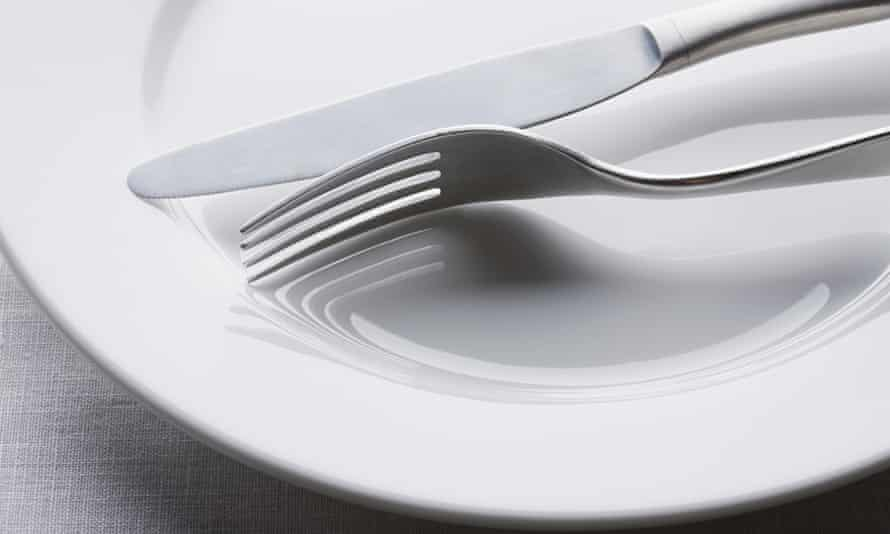 Knife and fork on empty white plate