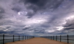 Storm clouds forming over a pier
