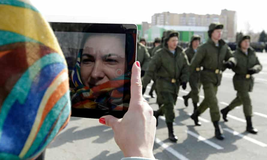 Russian servicemen march past a woman using a tablet during a military show