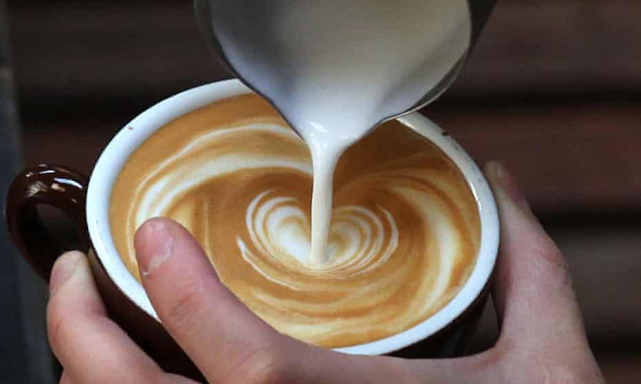 A barista pouring milk into a coffee