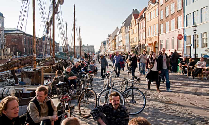 People sitting at along the waterfront of Nyhavn Canal, Copenhagen, Denmark