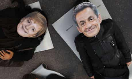 Demonstrators in Sarkozy and Merkel masks
