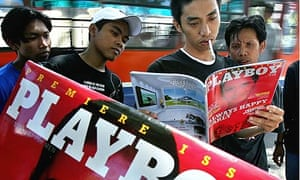 Young men read the first edition of Indonesia's no-nudes Playboy magazine in Jakarta in 2006