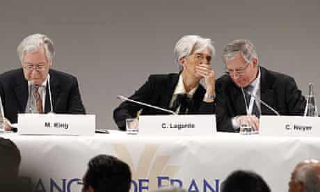 IMF chief Christine Lagarde whispers to France's central bank governor Christian Noyer