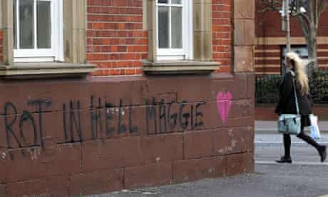 "A woman walks past graffiti that reads """