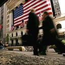 Commuters walk past New York Stock Exchange. Photograph: Spencer Platt/Getty
