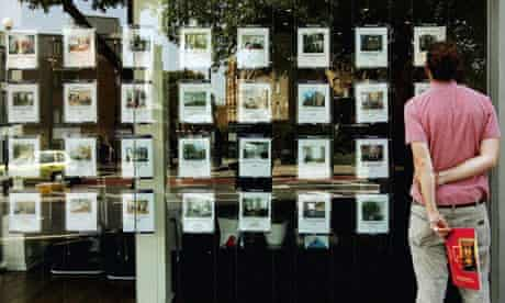 A man looking in the window of an estate agent
