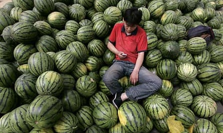 Watermelon vendor uses his mobile phone at a market in Taiyuan