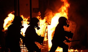 Riot policemen silhouetted in front of a burning kiosk during clashes in Athens