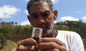 Antonio Ramos dos Santos holds up picture of son Herminio Cardoso dos Santos