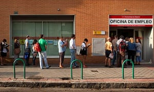 Unemployed people queue outside an unemployment registry office in Madrid