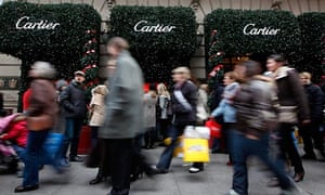 Shoppers walk up Fifth Avenue in front of the Cartier building
