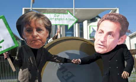 -Protesters dressed as German Chancellor Angela Merkel and French President Nicolas Sarkozy