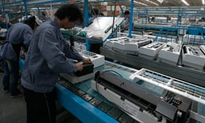 Employees work at a production line in a factory in Zhongshan, southern China