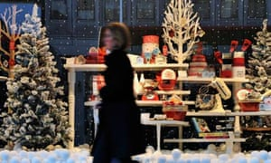 A shopper walks past a department store with a festive display, London, UK