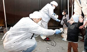Officials in protective gear check for radiation on children near the Fukushima nuclear plant