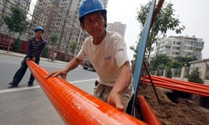 Workers move piping at a construction site in Beijing, China