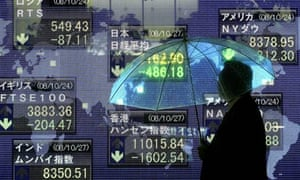 A man walks past an electronic board showing the closing price of Japan's Nikkei on October 27, 2008