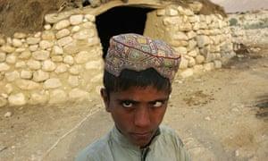 Pakistani boy outside a traditional family home