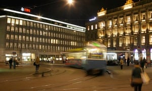 A tram drives past the offices of Swiss banks UBS and Credit Suisse at Paradeplatz square in Zurich