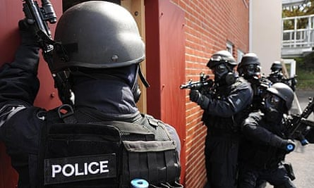 A British police SWAT team practice a house entry technique.