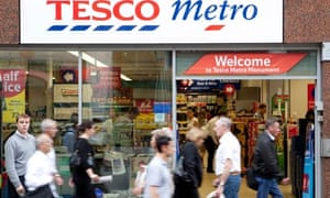 Shoppers walk in front of a Tesco Metro store
