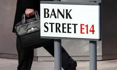 A worker passes a sign for Bank Street in Canary Wharf in London