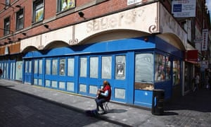 A busker plays outside a closed down shop in Liverpool