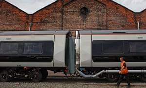 A worker walks alongside a Bombardier railway carriage at its Derby factory