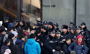 Police jostle with shoppers outside an Apple store in Beijing