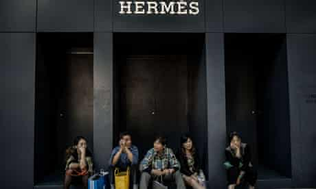 Chinese visitors from the mainland sit in front of a luxury shop in Hong Kong