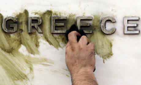 A worker cleans graffiti outside the Greek central bank's headquarters in Athens