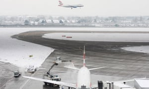 A British Airways plane is de-iced and cleared of snow at Terminal 5 of Heathrow Airport in