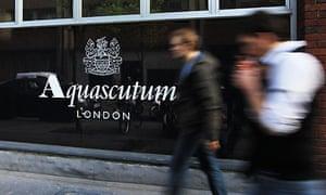 Pedestrians walk past an Aquascutum building in central London