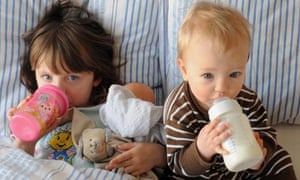 Little girls drinking from their bottles in bed