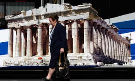 A woman walks past a bus featuring a picture of the temple of the Parthenon in Athens, 22 May 2012.