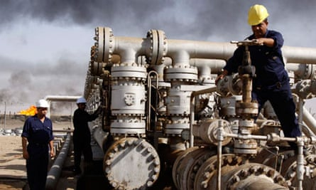 Iraqi workers are seen at the Rumaila oil refinery, near the city of Basra