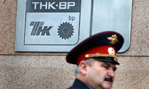 A police officer walks past a plaque of the oil firm TNK-BP at its headquarters in Moscow